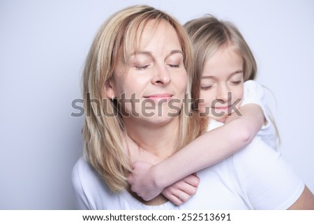 A mother with is daughter over gray background - stock photo