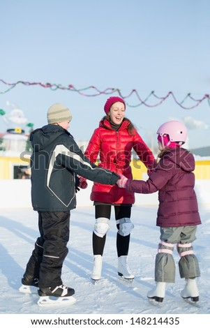A mother with two children are skating on the outdoor skating rink in winter - stock photo