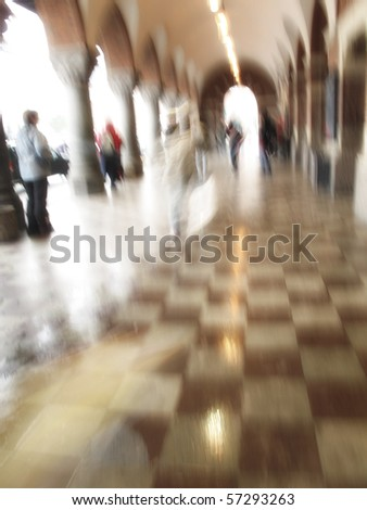 A motion and lens blurred image of people at the train station