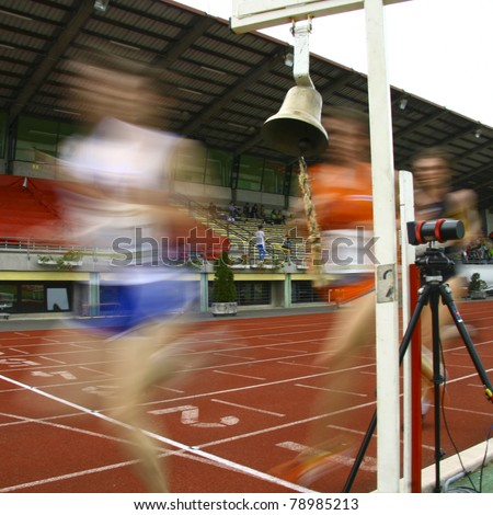 A motion blur of the runners crossing the finish line. - stock photo