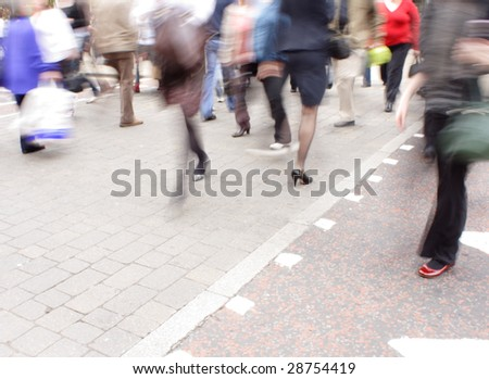 A motion blurred crowd of shoppers at a pedestrian crossing. Copyspace bottom left.
