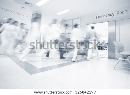 A motion blurred photograph of a patient on stretcher or gurney being pushed at speed through a hospital corridor. - stock photo