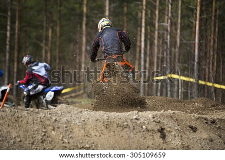 A motorcross driver accelerating from the curve on offroad track in the summer in Finland.