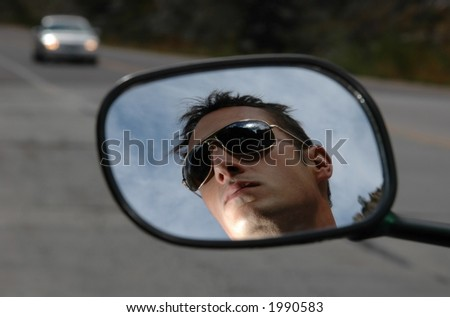 A motorcycle riders reflection in the mirror as he rides up a canyon rode - stock photo