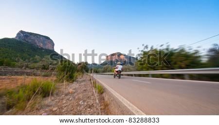 A motorcyclist cruising through the mountains - stock photo