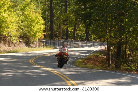 A motorcyclist driving along a winding road in the forest - stock photo