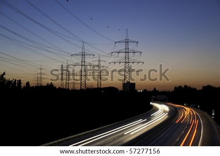 A motorway at dusk with electricity pylons