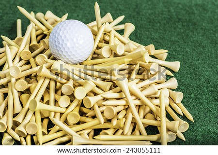 A mound of golf tees with a white ball sitting on top - stock photo