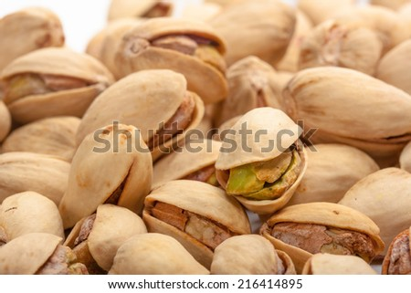 A mound of pistachio nuts on a white background - stock photo