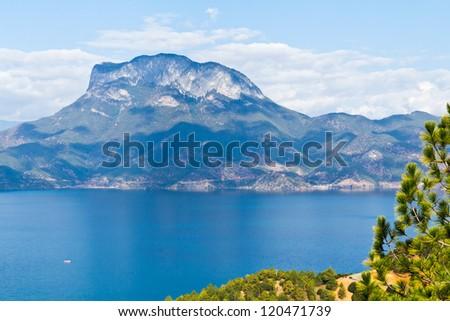 A mountain beside a blue lake - stock photo