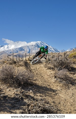 a mountain biker leans into a turn in the desert foothills with mountain in the background and copy space - stock photo