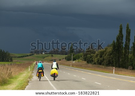 A mountain biker rides along a winding asphalt track in a valley among fields on a background of sky with clouds in New Zealand