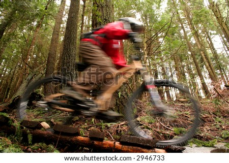 A mountain biker speeds over a wooden bridge. - stock photo