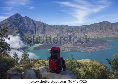A mountain hiker or trekker takes a break to enjoy beautiful view on top of a mountain. - stock photo