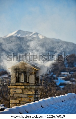 A mountain house roof with smoking chimney - stock photo