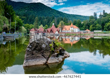 A mountain lake Ciucas at day. Reflection in the lake of the buildings, and green trees. Romania. Transylvania.