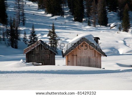 A mountain landscape (Dolomites, Italy) with a chalet in the snow. - stock photo