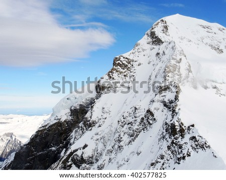A mountain peak at Jungfrau, Switzerland. The mountain in this photo looks like a human face looking up to the sky.