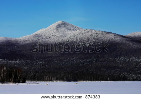 A mountain peak in the Vermont winter behind a frozen lake. - stock photo