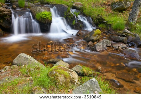 A mountain river with waterfalls in the spring season - stock photo