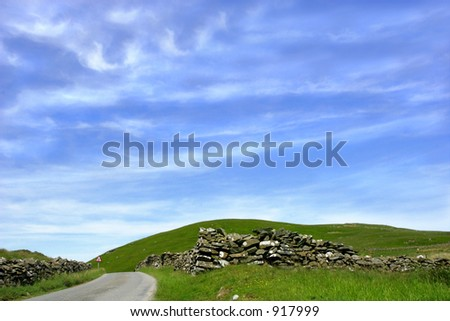 A mountain road with stone walls on either side and a blue sky and clouds. - stock photo