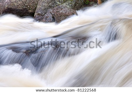 A mountain stream in Colorado flowing over rocks. - stock photo