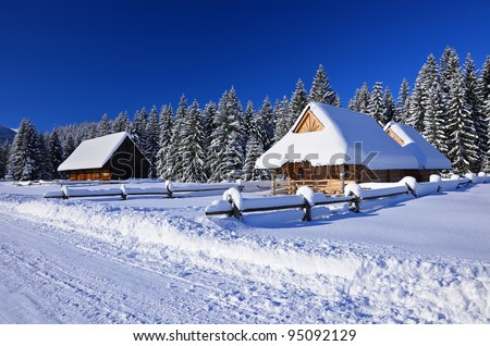 A mountain wooden huts covered with fresh snow  in Chocholowska valley - Tatra Mountains - stock photo