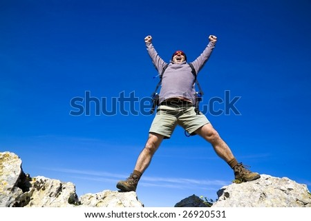 A mountaineer reaching the summit, and shouting with joy, for his achievement - stock photo