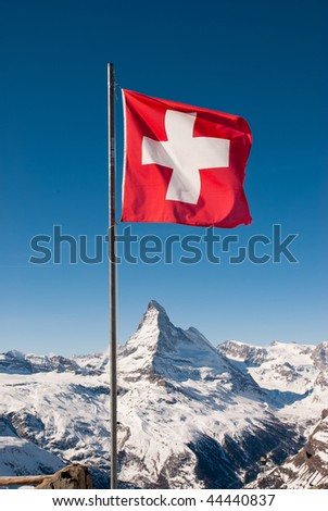 A mountaintop view of the national flag of Switzerland with the Matterhorn in the background - stock photo