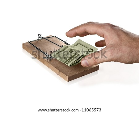 A mousetrap attracting a greedy hand. Can be used as a concept for risky investing. - stock photo