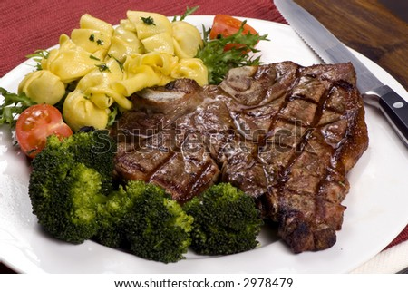 A mouth watering porterhouse steak with fresh vegetables and pasta - stock photo