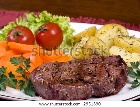 A mouth watering tenderloin steak with fresh vegetables and potatoes - stock photo