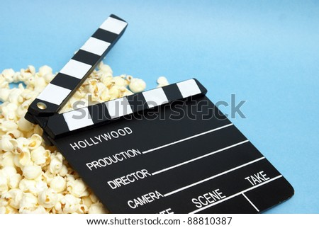 A movie clapboard rests on a pile of fresh popcorn. - stock photo