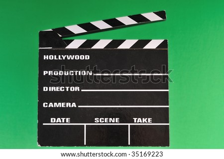 a movie marker or clapper board set against a green screen - stock photo