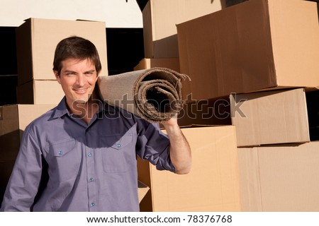 A moving an carrying a carpet with cardboard boxes in the background - stock photo