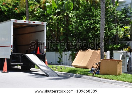 A Moving Van On Street With Ramp, Boxes And Household Furnishings - stock photo