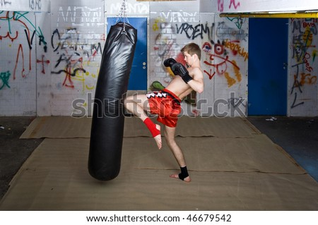 A muay thai fighter giving a knee kick during a practice - stock photo