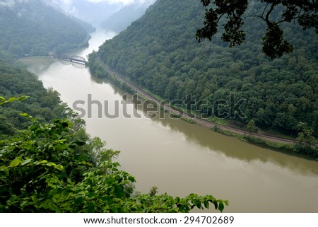 A muddy and rain swollen New River winds through a wooded valley near train tracks near Hawk's Nest State Park in southern West Virginia - stock photo