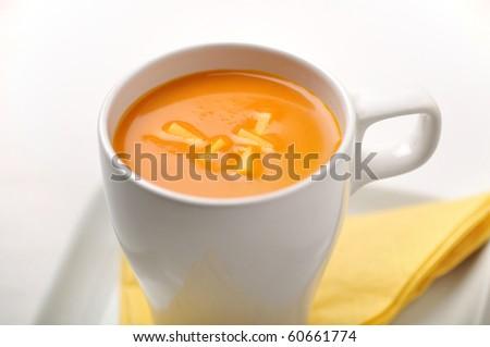 A mug full of pumpkin soup - stock photo