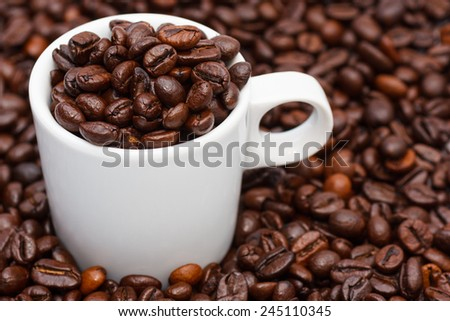 A mug full of roasted coffee beans - stock photo