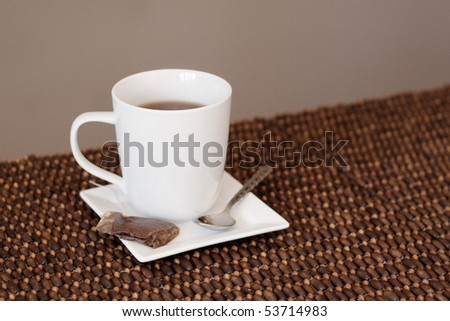 A mug full of tea with a teabag and spoon on a saucer. Clean and modern styling. - stock photo