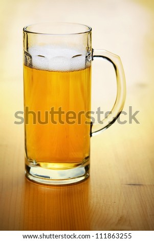 A mug of beer on wooden table