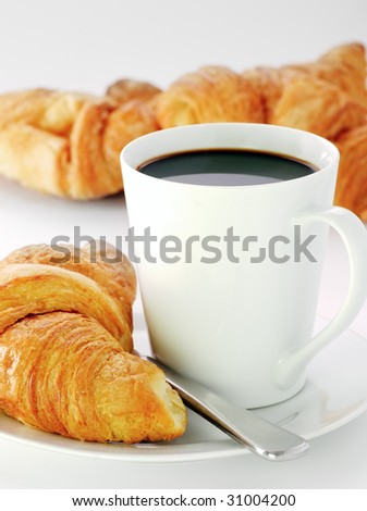 a mug of black coffee with fresh croissants - stock photo