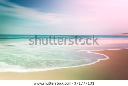 A multi-colored seascape with opposing light and dark vignettes.  This is a soft-focus image combining a long exposure with panning motion. - stock photo