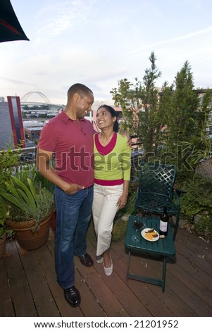 A multi-ethnic couple standing on a wooden deck.  They are surrounded by plants and are smiling.  The man has his arm around the woman.  They are looking at each other.  Vertically framed shot. - stock photo