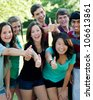 A multi-ethnic group of teenage friends outside with thumbs-up - stock photo
