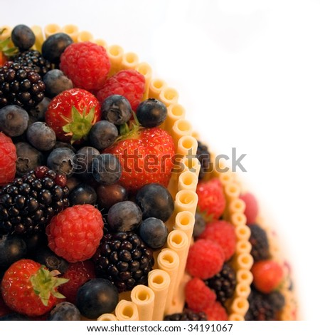 A multi-layered wedding cake with raspberries, blackberries, blueberries, strawberries and white chocolate sticks over a white background - stock photo