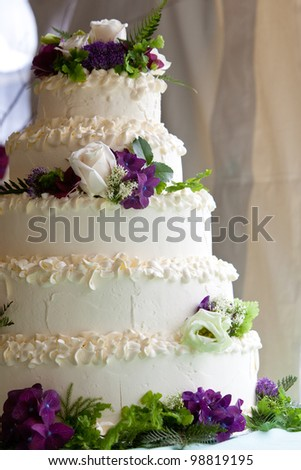 A multi level wedding cake with purple and white flowers - stock photo