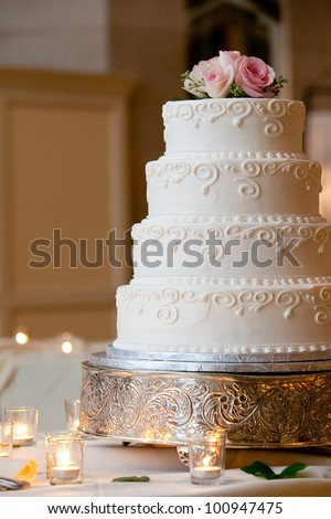 a multi level white wedding cake on a silver base and pink flowers on top - stock photo