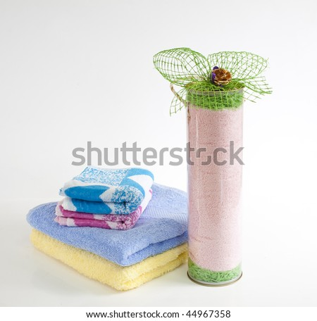 a multicolored towels stacked and decorated in transparent tube - stock photo